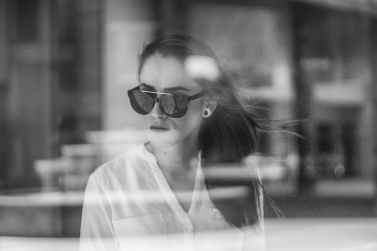 grayscale photo of woman through a glass window
