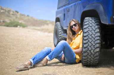 woman in yellow polo shirt sitting on ground leaning on blue vehicle at daytime